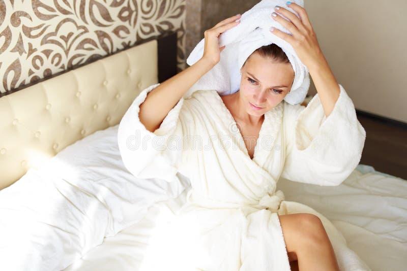 Schönes Brunettemädchen mit einem Tuch auf ihrem Kopf im Bett Sie nahm eine Dusche lizenzfreies stockfoto