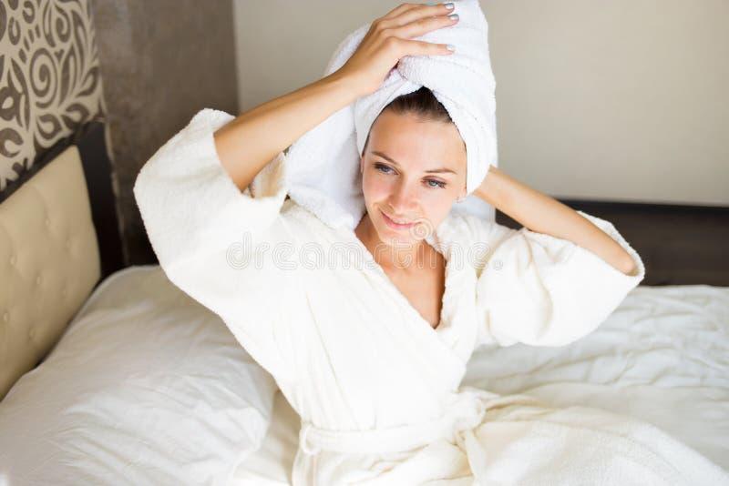 Schönes Brunettemädchen mit einem Tuch auf ihrem Kopf im Bett Sie nahm eine Dusche Uhr als Kaffeetasse, Zeitung und Stift stockbilder