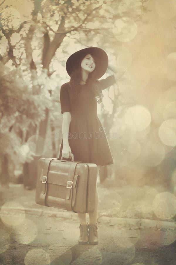 Schönes Brunettemädchen mit Koffer stockbild