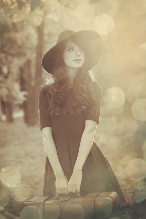 Schönes Brunettemädchen mit Koffer stockfoto