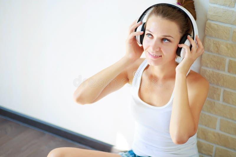 Schönes Brunettemädchen mit Kopfhörern hörend Musik beim Sitzen auf dem Boden in einem leeren Raum auf der weißen Wand lizenzfreies stockbild