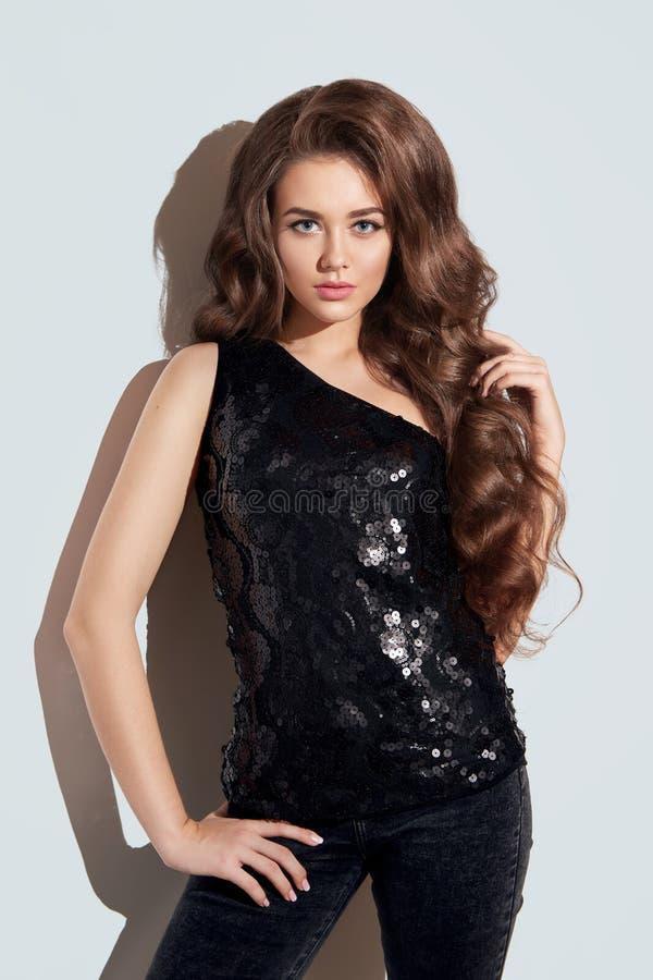 Schönes Brunettemädchen mit lang und glänzendes gelocktes Haar des Volumens stockbild