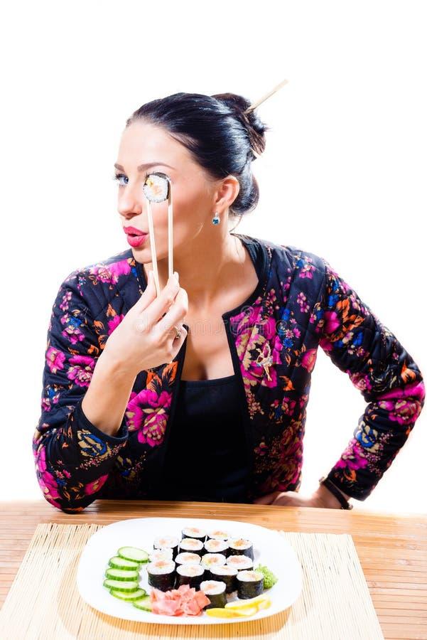 Schönes Brunettemädchen mit rote Lippenlustigen haltenen Essstäbchen und den schmecken Sushi, die Kamera auf weißem Hintergrundpo lizenzfreies stockfoto