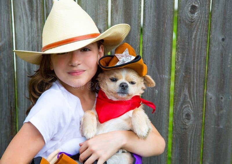 Schönes Cowboykindermädchen, das Chihuahua mit Sheriffhut hält lizenzfreies stockbild