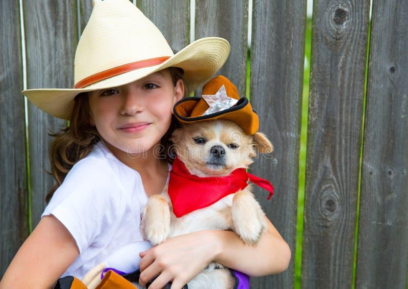 Schönes Cowboykindermädchen, das Chihuahua mit Sheriffhut hält stockfotografie