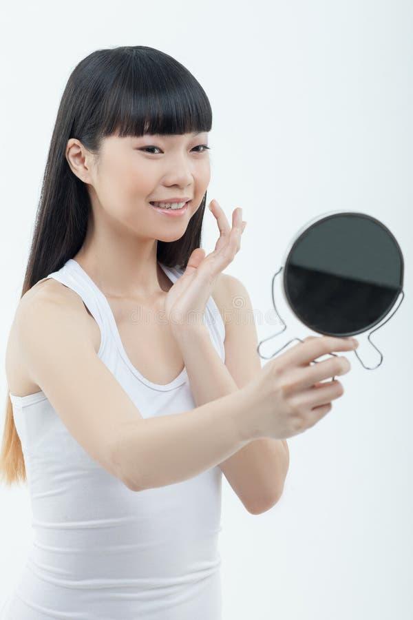Schönes dünnes chinesisches Mädchen tut Make-up stockfotos