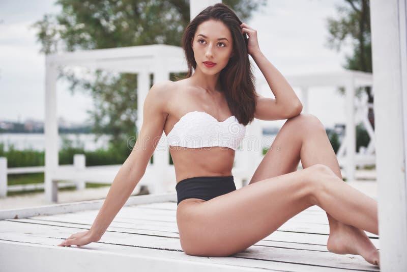 Schönes dünnes Luxusmädchen im Bikini auf dem Sandstrand auf einer Tropeninsel Sexy gebräunter Körper und perfekte Zahl stockbilder