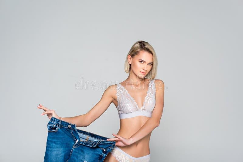 schönes dünnes Mädchen in der Wäsche, die große Jeans hält, lizenzfreies stockbild