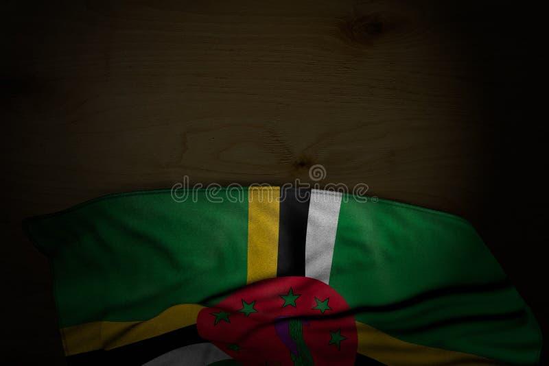Schönes düsteres Bild von Dominica-Flagge mit großen Falten auf dunklem Holz mit freiem Raum für Text - irgendeine Feierflagge 3d vektor abbildung