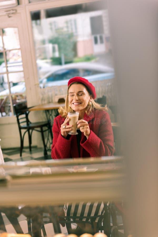 Schönes Damengefühl entspannte sich, etwas Kaffee während des Bruches trinkend lizenzfreie stockfotos