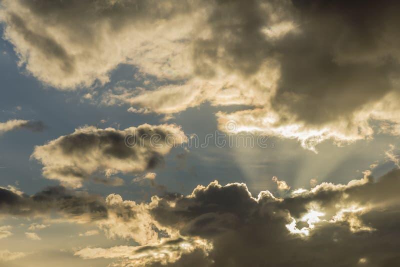 Schönes Detail eines drastischen Himmels, in dem die Sonne durch die Wolken späht lizenzfreies stockbild
