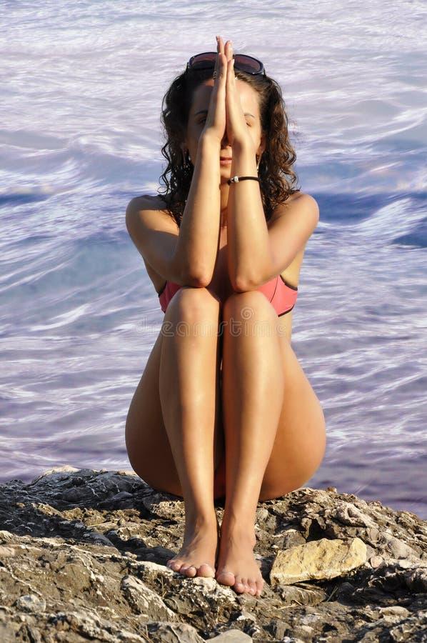 schönes dunkelhaariges Mädchen, das auf dem Strand sitzt stockfotos