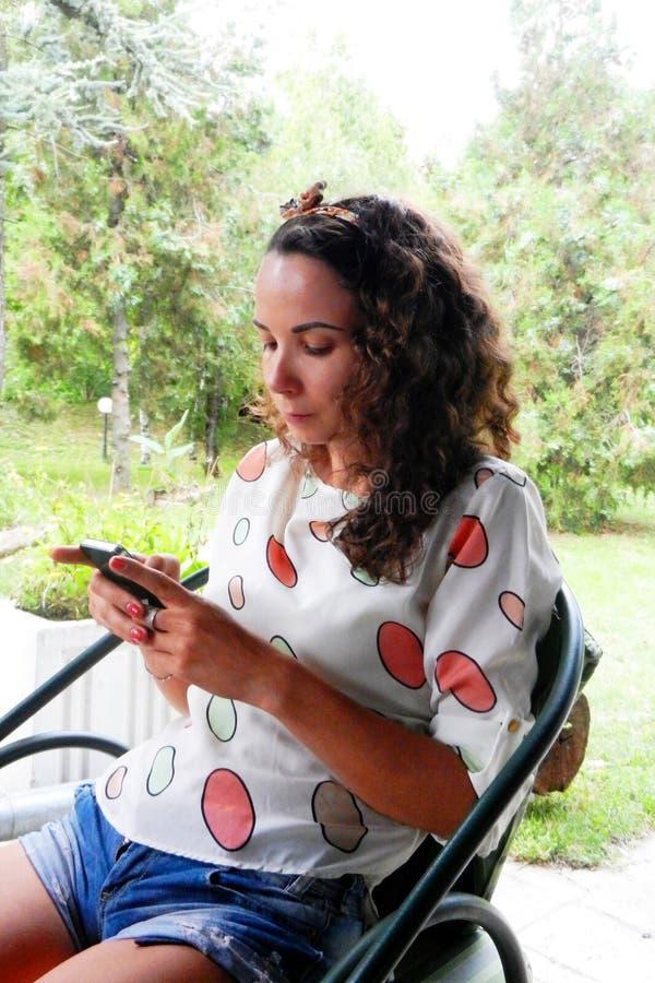 Schönes dunkelhaariges Mädchen im Park mit einem Handy stockfoto