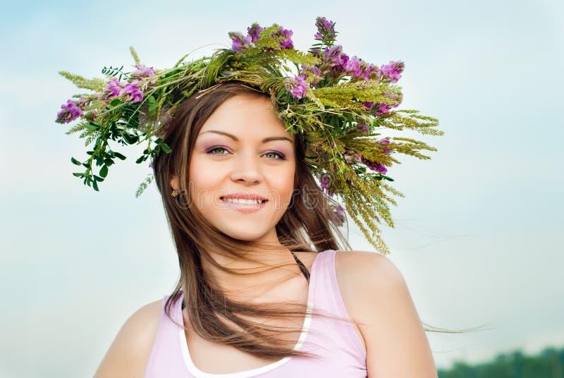 Schönes e-Mädchen in einem Wreath der Blumen lizenzfreies stockfoto