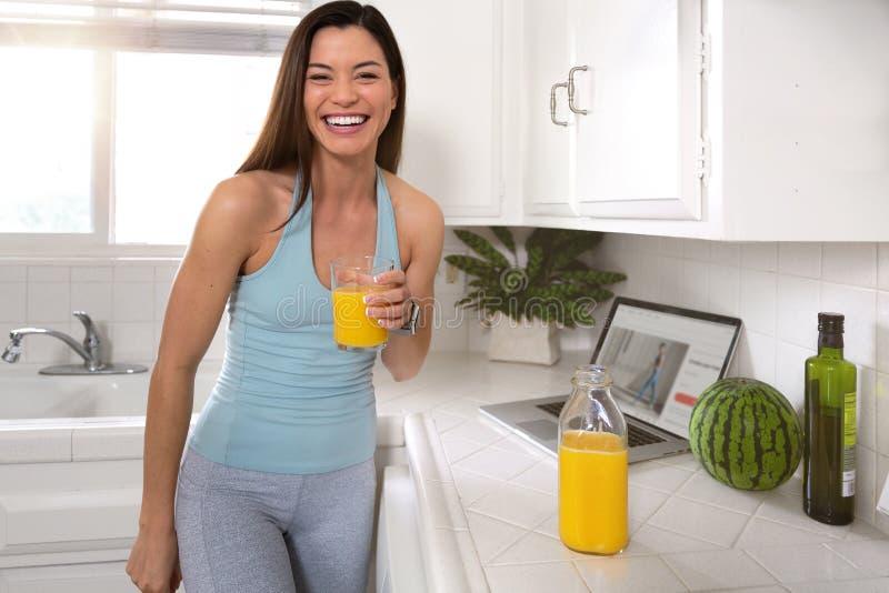 Schönes echtes Lebensstilporträt einer gesunden und glücklichen Frau mit Glas Orangensaft, Wellness, Eignung, Gesundheit stockfotografie