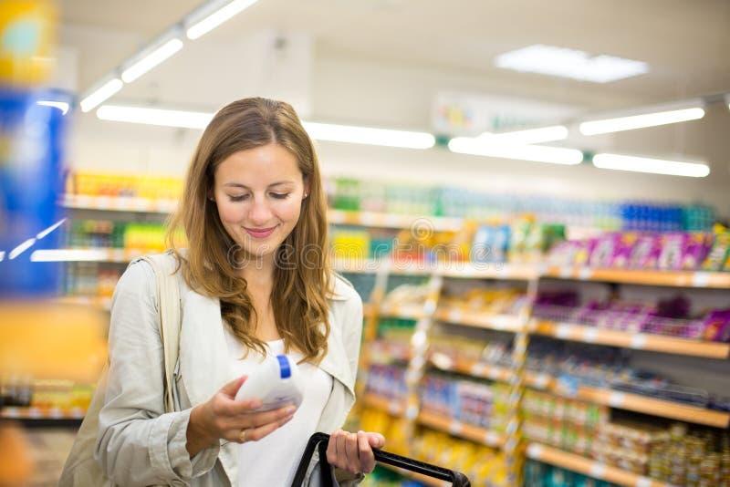 Schönes Einkaufen der jungen Frau in einem Gemischtwarenladen stockfotografie