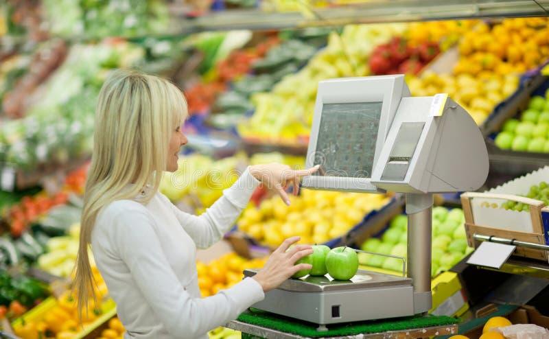 Schönes Einkaufen der jungen Frau für Gemüse lizenzfreie stockfotos