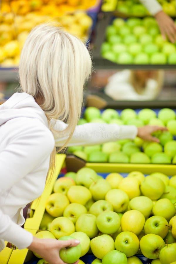 Schönes Einkaufen der jungen Frau für Gemüse stockfoto