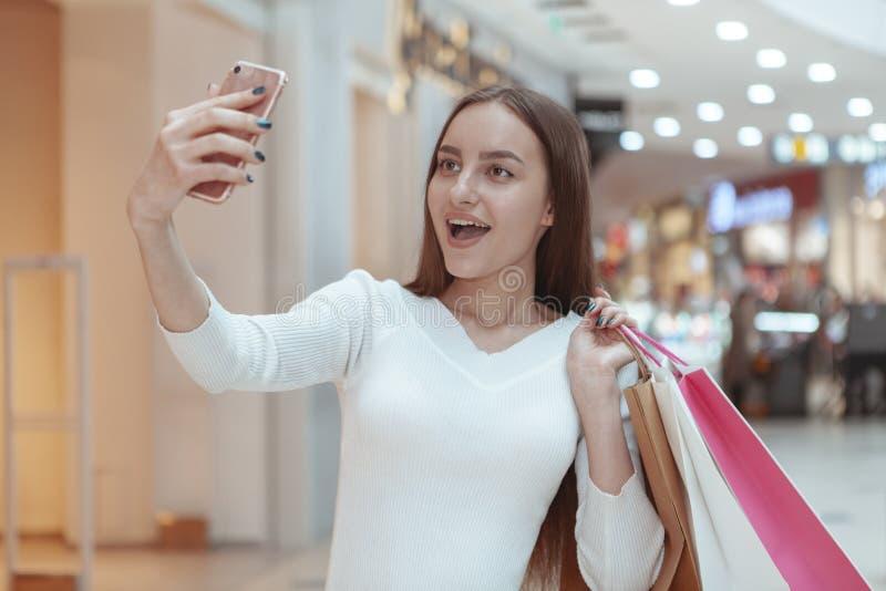 Schönes Einkaufen der jungen Frau am lokalen Mall lizenzfreie stockbilder