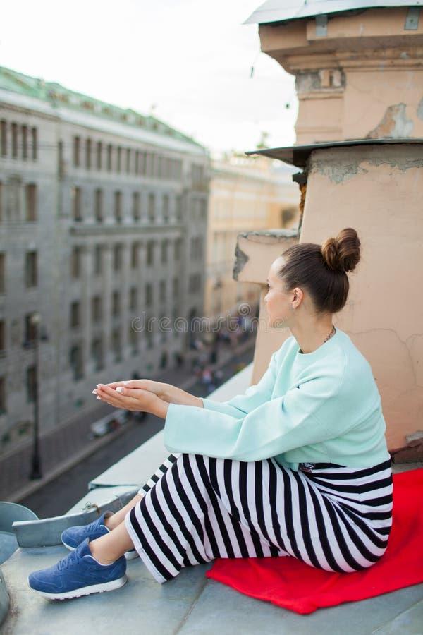 Schönes einsames Mädchen, das auf dem Dach in der alten Stadt von Träumen sitzt lizenzfreies stockfoto
