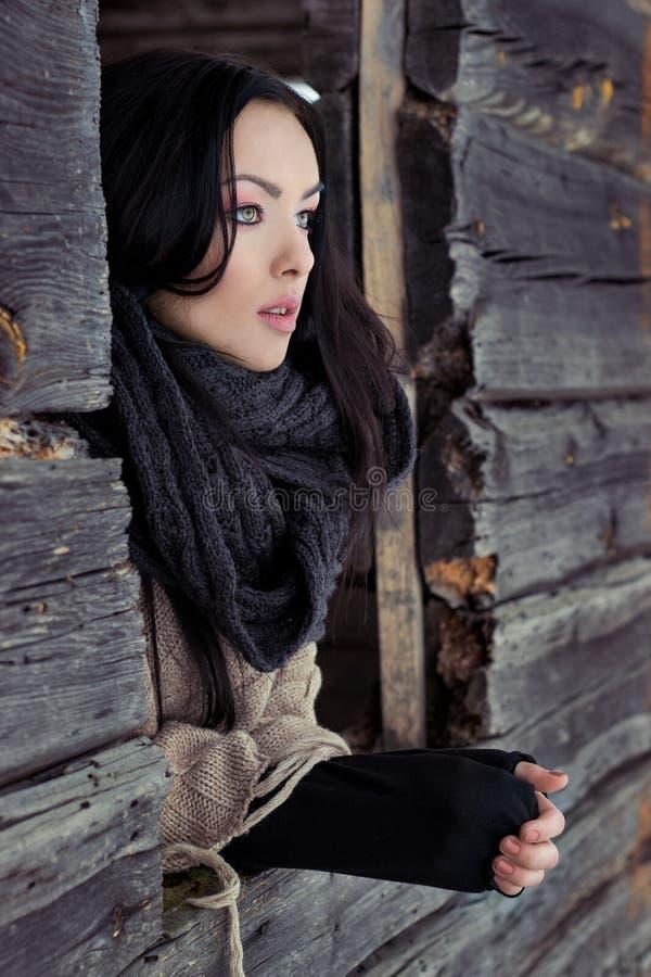 Schönes einsames Mädchen schaut heraus das Fenster des Hauses an einem eisigen Wintertag des Winterfreien raumes stockbild