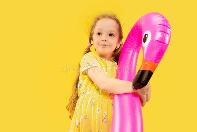 Schönes emotionales kleines Mädchen lokalisiert auf gelbem Hintergrund stockbild