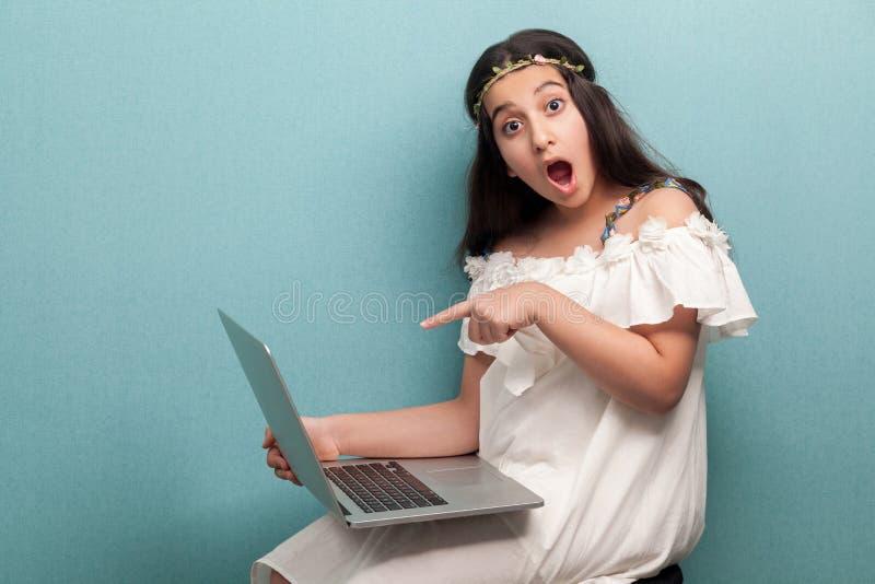 Sch?nes entsetztes Jugendlichm?dchen mit dem langen schwarzen Haar im wei?en Kleid, das mit Laptop sitzt, auf Anzeige zeigt und K lizenzfreie stockfotografie