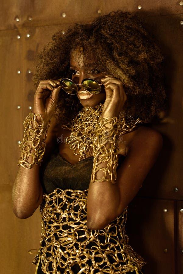 Schönes erstaunliches Porträt einer jungen Frau des Afroamerikaners mit dem Afrohaar Mädchen, das moderne Goldsonnenbrille trägt stockbilder