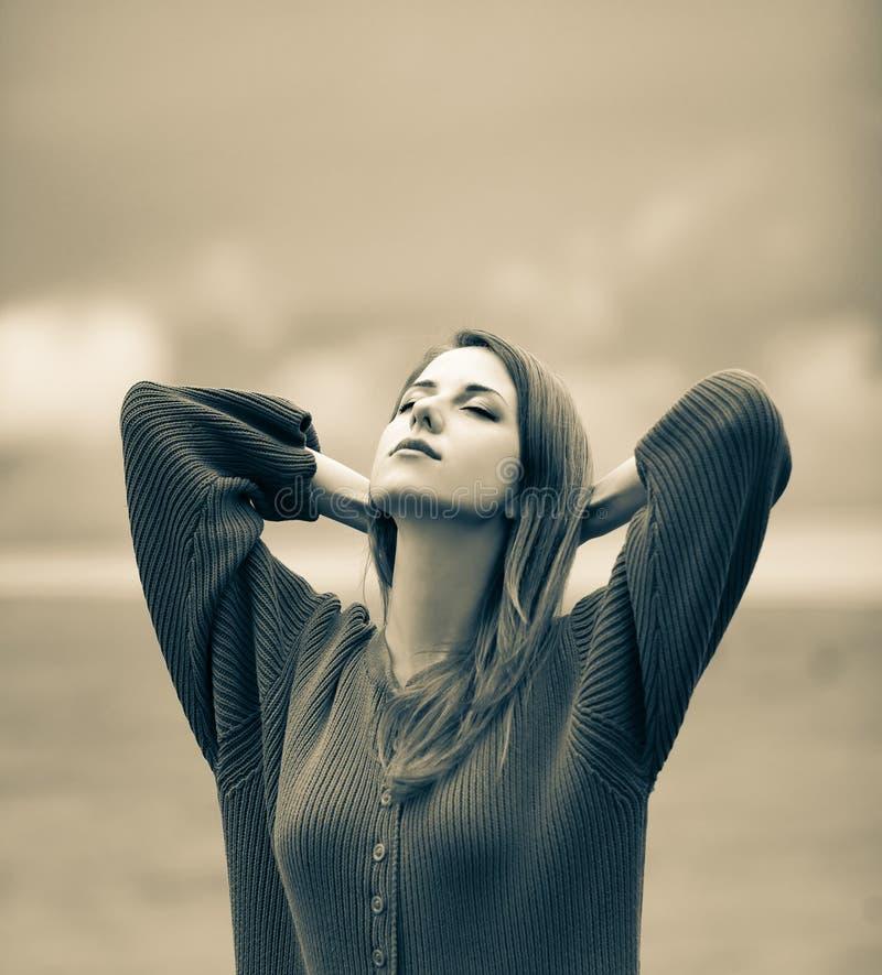Schönes erwachsenes Mädchen in der Strickjacke am Weizenfeld stockfotografie