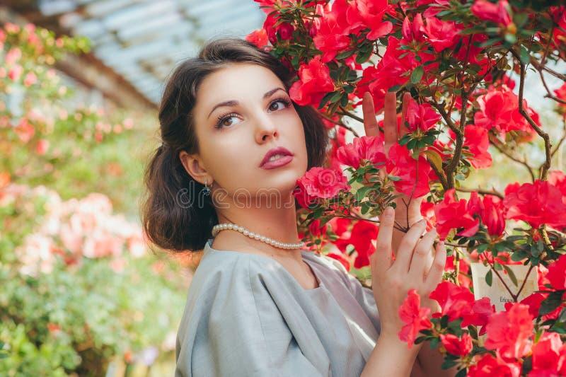 Schönes erwachsenes Mädchen in einem Azaleengewächshaus träumend in einem schönen Retro- Kleid und in einem Hut stockfotos