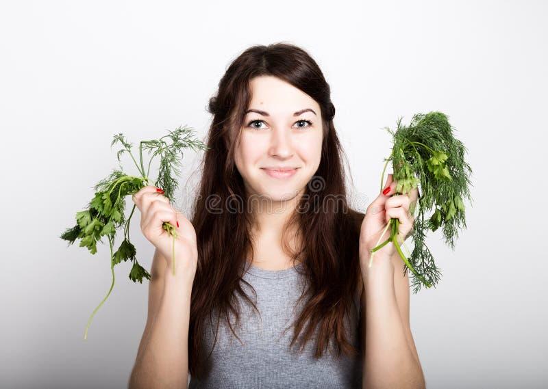 Schönes Essen der jungen Frau Gemüse Wahl, Petersilie oder Dill gesundes Lebensmittel - starkes Zahnkonzept stockbild