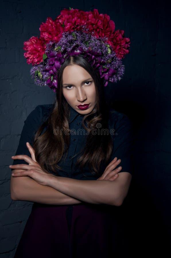 Schönes femme fatale in einem Kopfschmuck von der frischen bunten Blume lizenzfreie stockbilder
