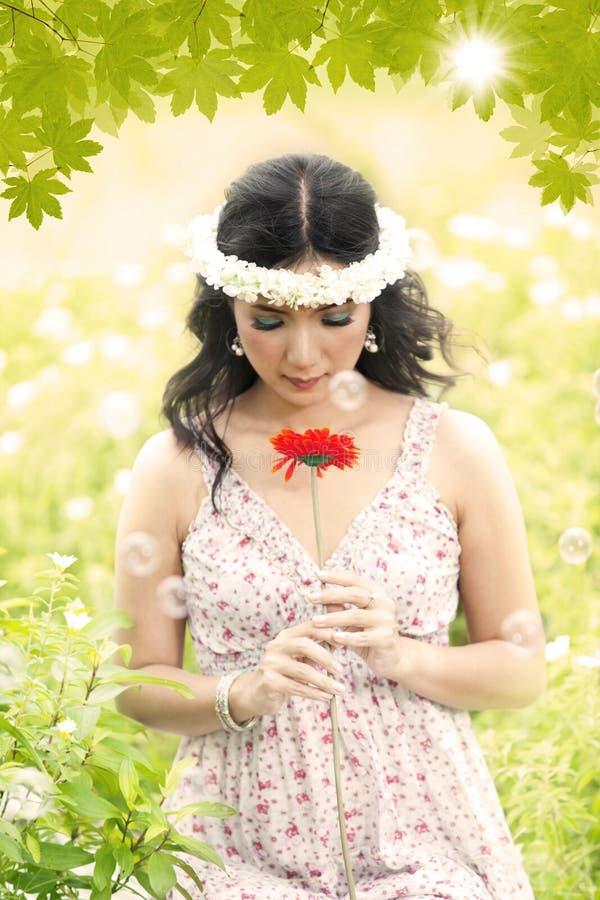 Schöner Engel mit roter Blume lizenzfreie stockbilder