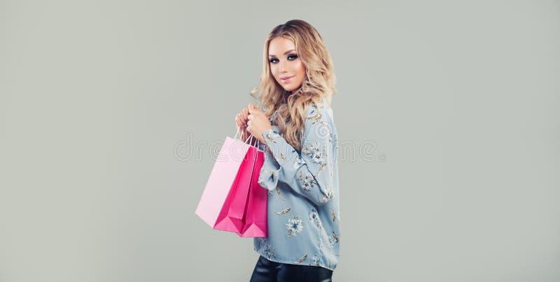 Schönes Fraueneinkaufen Mode-Modell, das Einkaufstaschen hält lizenzfreies stockfoto