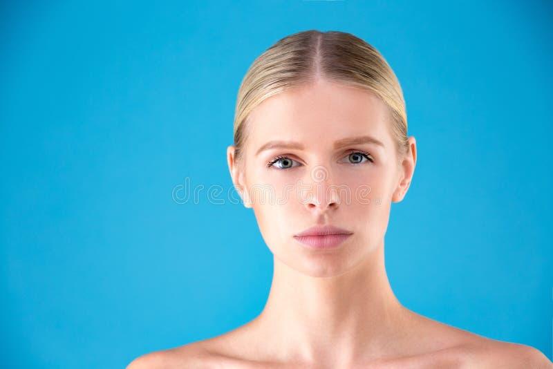Schönes Frauengesicht Schönheits-Porträt der Blondine der jungen Frau auf blauem Hintergrund Reines Schönheits-Modell Jugend-und  lizenzfreies stockfoto