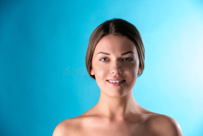 Schönes Frauengesicht Schönheits-Porträt von junge Frau Brunette, der auf blauem Hintergrund lächelt Reines Schönheits-Modell Jug stockfotos