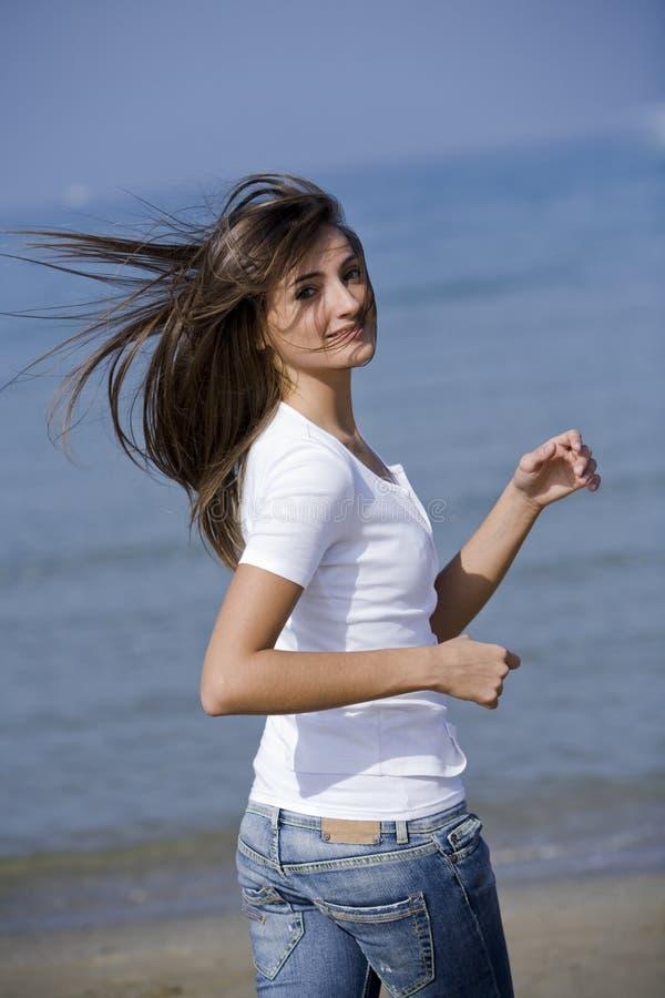 Schönes Frauenlaufen windblown auf dem Strand lizenzfreie stockbilder