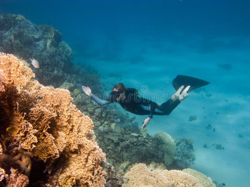 Schönes freediver Mädchen steigt entlang Korallenriff lizenzfreies stockbild
