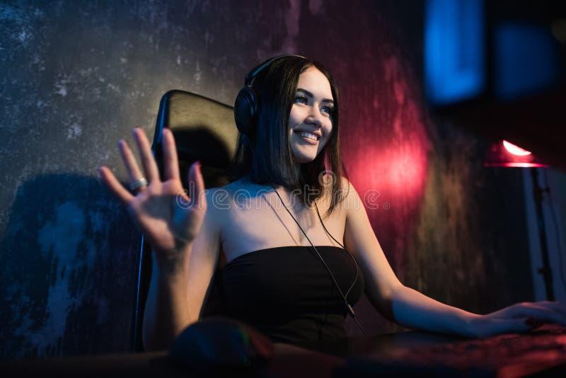 Schönes freundliches Progamer-Mädchen tut Videospiel Gameplay Strom, Tragenkopfhörer-Gespräche und Chate mit ihren Fans und lizenzfreie stockfotografie