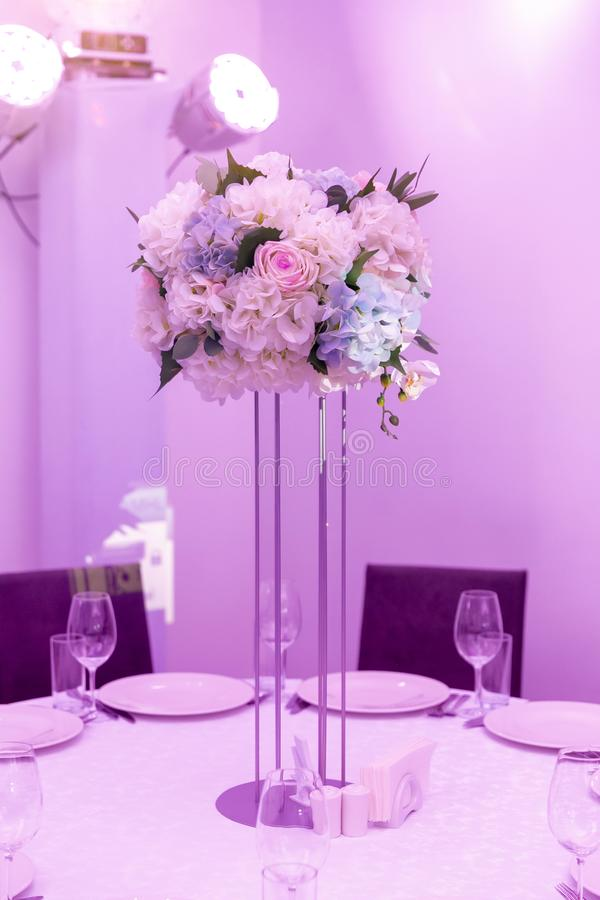 Schönes Gedeck mit Anordnung der Tonware und der weißen Blume in einem Vase auf einem hohen Stamm für eine Partei, Hochzeitsempfa lizenzfreies stockfoto