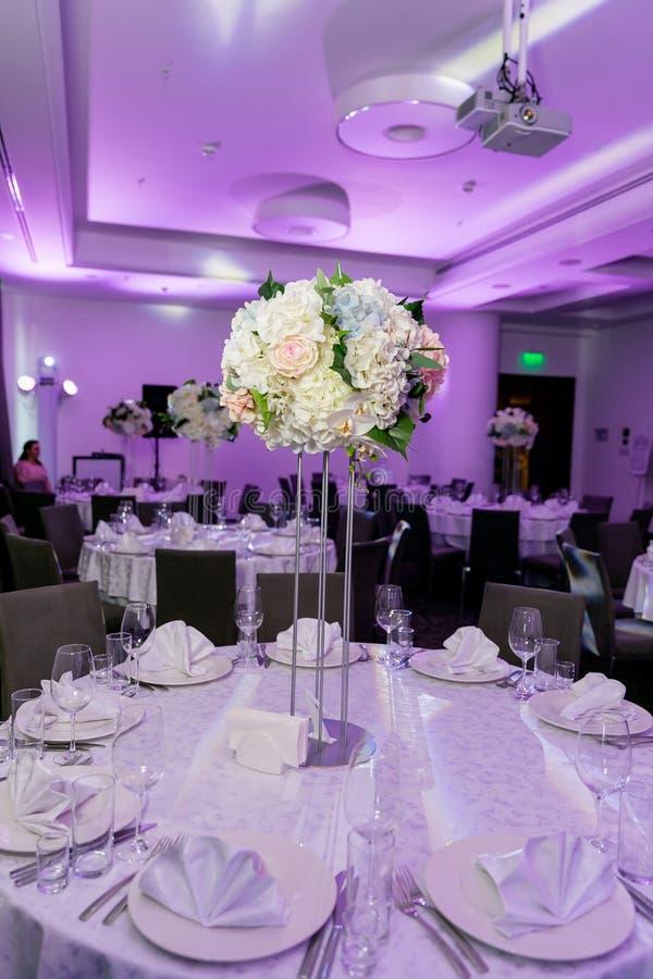 Schönes Gedeck mit Anordnung der Tonware und der weißen Blume in einem Vase auf einem hohen Stamm für eine Partei, Hochzeitsempfa stockfotografie