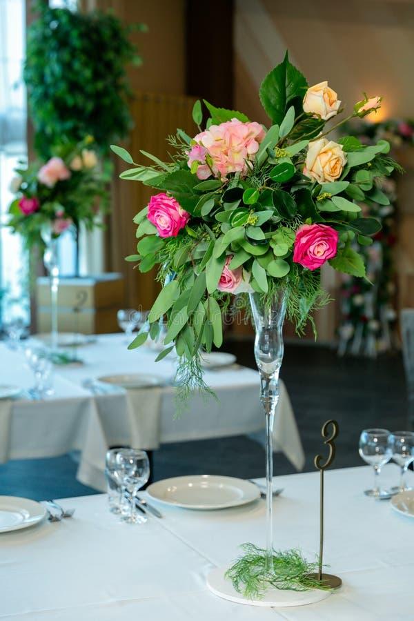 Schönes Gedeck mit Tonwaren- und Blumenanordnung in einem Vase auf einem hohen Stamm für eine Partei, einen Hochzeitsempfang oder lizenzfreies stockfoto