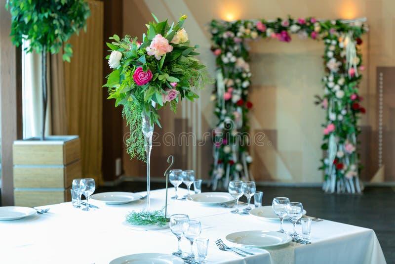 Schönes Gedeck mit Tonwaren- und Blumenanordnung in einem Vase auf einem hohen Stamm für eine Partei, einen Hochzeitsempfang oder stockbilder