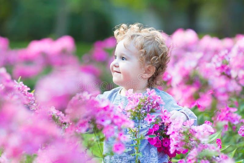 Schönes gelocktes Baby, das im Garten spielt lizenzfreie stockbilder