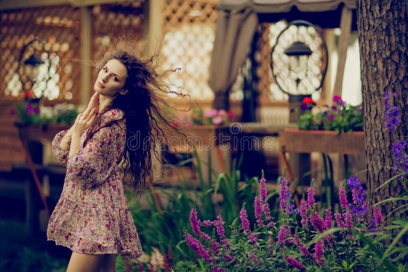 Schönes gelocktes Brunettemädchen mit sich entwickelnden Haar auf dem backgr lizenzfreie stockfotografie