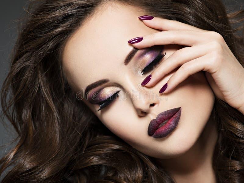 Schönes Gesicht der Frau mit kastanienbraunem Make-up und Nägeln lizenzfreies stockbild
