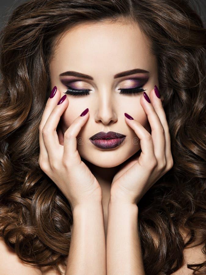 Schönes Gesicht der Frau mit kastanienbraunem Make-up und Nägeln stockfotos