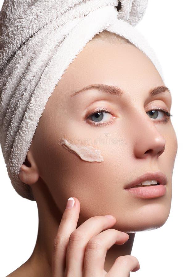 Schönes Gesicht der jungen Frau mit kosmetischer Sahne auf einer Backe Nahaufnahmeportrait getrennt auf Weiß Nahaufnahmeporträt l stockbilder