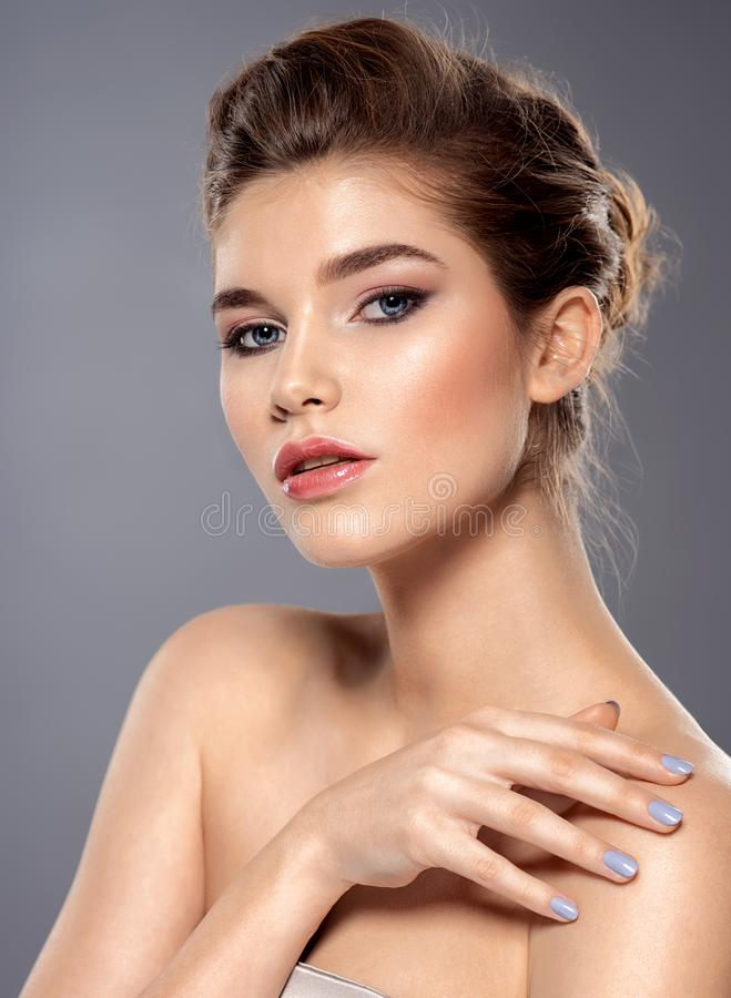 Schönes Gesicht der jungen kaukasischen Frau mit perfekter Gesundheitshaut - über grauem Hintergrund stockfotos