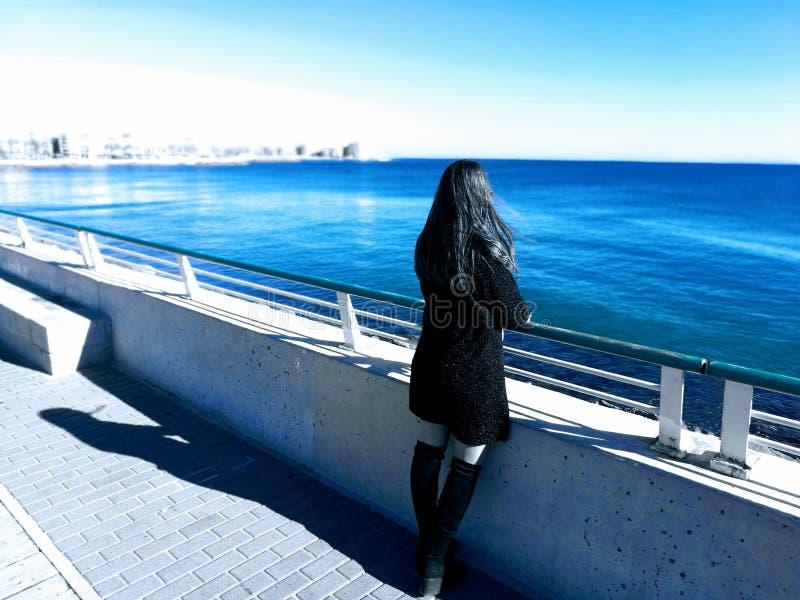 Schönes girlin Schwarzkleid, das entlang des Strandes anstarrt Traumweltkonzept lizenzfreie stockfotografie